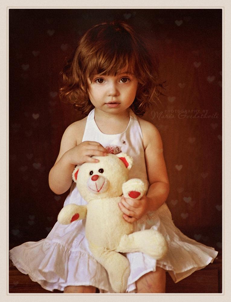Девочка в белом платье с белым медвежонком.